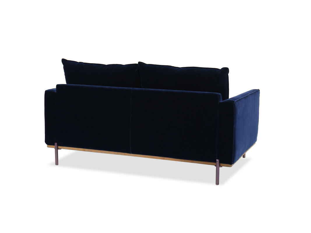 Loveseat is upholstered in super smooth velvet in a beautiful blue tone wood like accents on base add warm contrast to this living room furniture