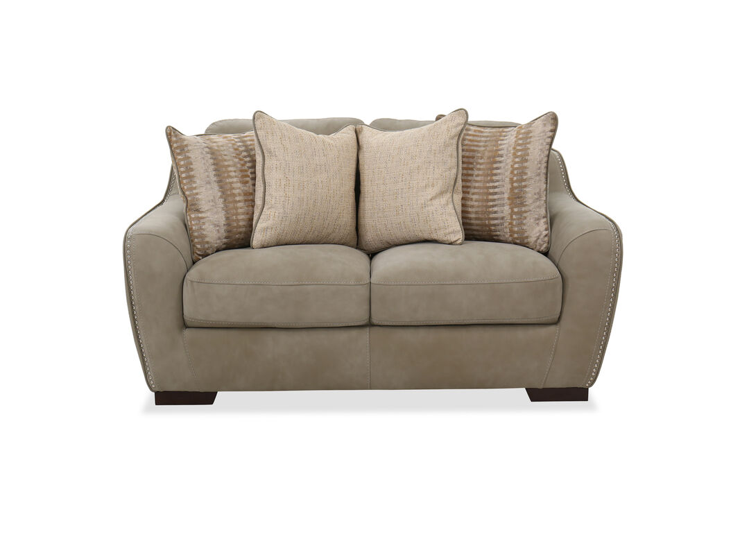 The shiny nailheads on the arms provide a polished touch to this living room furniture four throw pillows with welted edges and artsy patterns